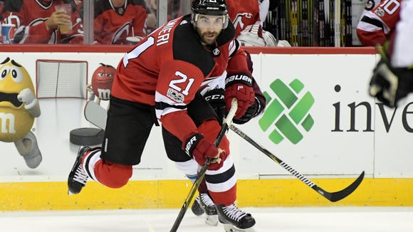 New Jersey Devils right wing Kyle Palmieri (21) passes the puck during the second period of an NHL hockey game against the Colorado Avalanche Saturday, Oct. 7, 2017, in Newark, N.J. (AP Photo/Bill Kostroun)