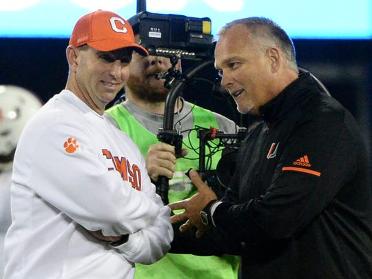 Clemson head coach Dabo Swinney, left, and Miami head coach Mark Richt talk before kickoff at the Dr.Pepper ACC football championship in Charlotte on Saturday.