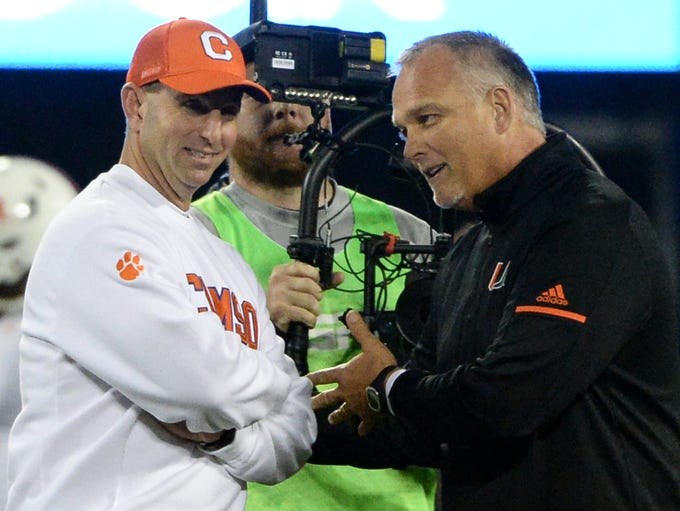 Clemson head coach Dabo Swinney, left, and Miami head