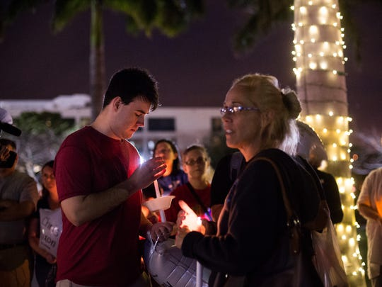 Noah Hilliard, 17, of Stuart, attends a candlelight vigil at Memorial Park in downtown Stuart on Monday, Feb. 19, 2018, to honor the victims of last week's mass shooting at Marjorie Stoneman Douglas High School in Parkland. The vigil, which was organized by Florida PTA, was one of several held simultaneously across the state.
