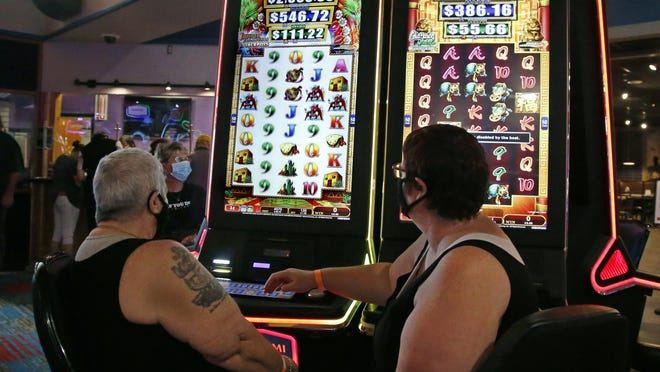 Gladys Whittington, left, and Sandy Christian, right, play at a gaming machine at Lucky Star Casino Friday, May 15, 2020, as Lucky Star Casino reopens after a temporary shutdown due to coronavirus concerns, in Concho, Okla. Employees are required to wear facial coverings while facial coverings are encouraged for casino guests.