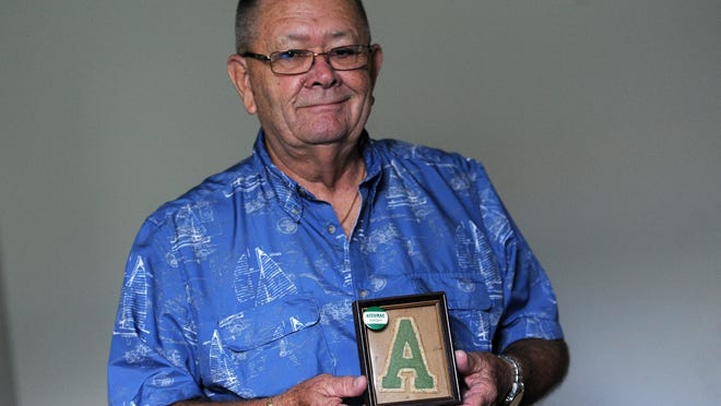 Tom Hopkins holds his father's framed varsity letter he received while attending Accomac High School in the 1930s. Hopkins attended the school as an elementary student in the 1950s and has a collection of memorabilia related to the former school.