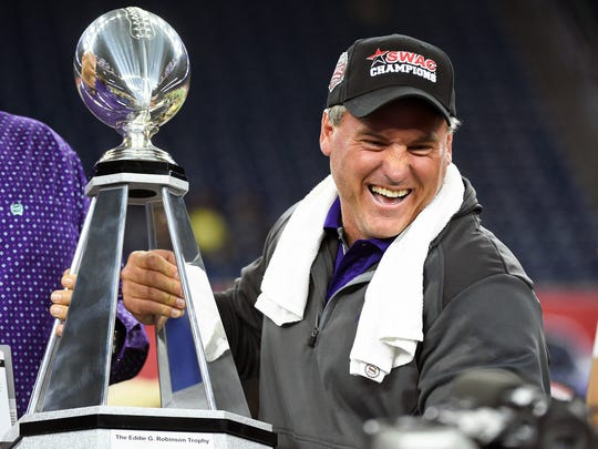 Alcorn State head coach Jay Hopson poses with the Eddie G. Robinson trophy after Alcorn State defeated Grambling State 49-21 in the SWAC Championship Game.