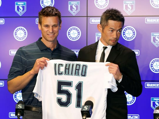 Ichiro Suzuki, right, holds up his jersey with general manager Jerry Dipoto on Wednesday at the Mariners' spring training baseball complex  in Peoria, Ariz. Suzuki signed a one year deal in his return to the Mariners.