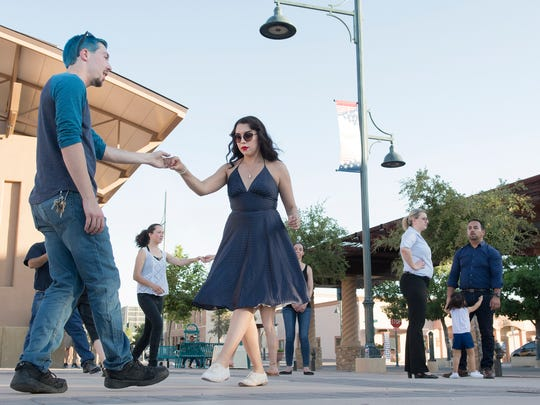 Christopher Lininger, left, and Alyxandra Shea, walk the group through some basic moves Tuesday, July 17, 2018, during the Swing on the Plaza event sponsored by the Downtown Las Cruces Partnership.