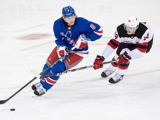 New York Rangers defenseman Jacob Trouba (8) skates against New Jersey Devils right wing Joey Anderson (14) during the third period of an NHL hockey game, Saturday, March 7, 2020, at Madison Square Garden in New York. (AP Photo/Mary Altaffer)
