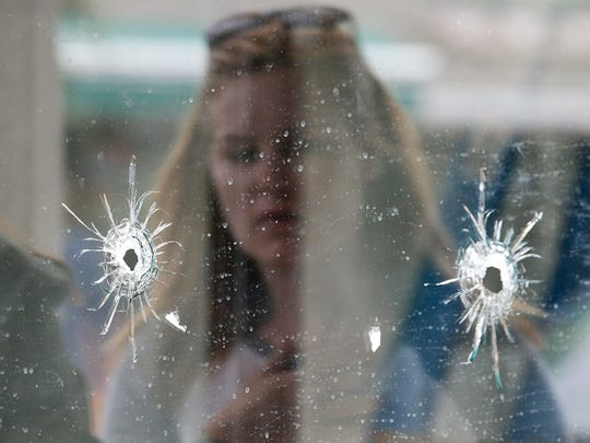 In this May 24, 2014, file photo, a woman looks at the bullet holes on the window of IV Deli Mark where a mass shooting took place near the University of California, Santa Barbara campus, in the Isla Vista beach community.