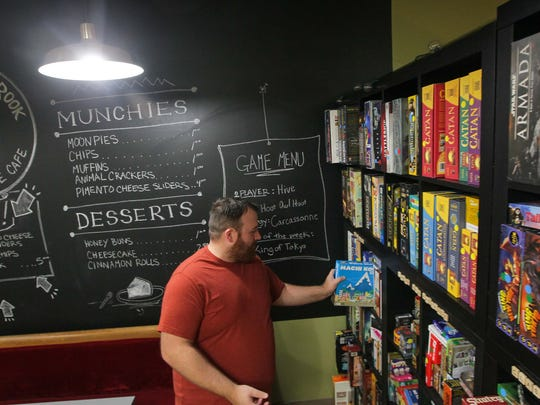 Seth Wright of The Crooked Rook Cafe looks over one of the 350 games on Saturday at the store in Anderson.