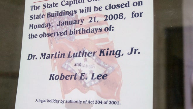 In this Jan. 16, 2008, file photo, a note is posted on a door at the Arkansas state Capitol in Little Rock, Ark., indicating state offices will close in observance of civil rights leader Martin Luther King Jr. and Confederate General Robert E. Lee's birthdays. Lee's birthday is no longer part of MLK day, leaving Mississippi and Alabama as the only states that jointly celebrate King and Lee.