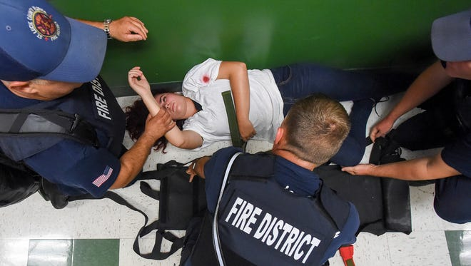 Tiffany Coronel, 17, of Port St. Lucie acts as a shooting victim Wednesday, July 11, 2018, as St. Lucie County Fire Rescue personnel conduct S.A.V.E. (Swift Assisted Victim Extraction) training at Renaissance Charter School of St. Lucie in Port St. Lucie.