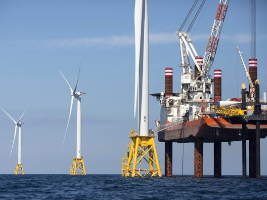 A lift boat, right, that serves as a work platform, assembles a wind turbine off Block Island, R.I., Monday, Aug. 15, 2016. Deepwater Wind's $300 million five-turbine wind farm off Block Island is expected to be operational this fall. (AP Photo/Michael Dwyer)