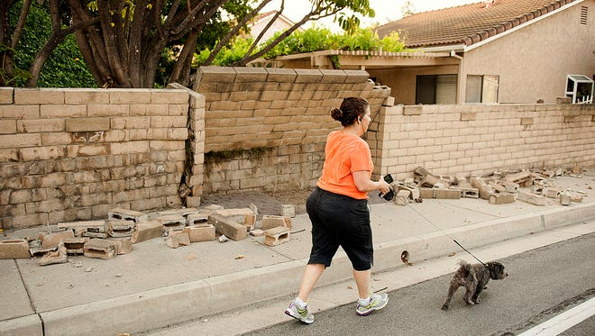 A woman walks her dog past a broken block wall in Fullerton, Calif., on  March 29 after an earthquake hit Orange County Friday night.