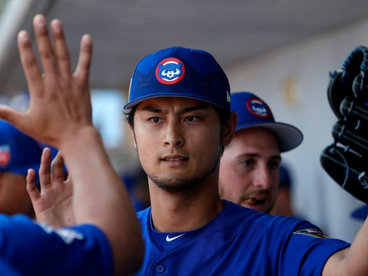 Chicago Cubs pitcher Yu Darvish high-fives teammates in the dugout during the second inning of a spring training baseball game against the Los Angeles Dodgers, Tuesday, March 6, 2018, in Mesa, Ariz. (AP Photo/Matt York)