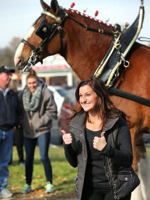 Jennifer Reeves of Indianapolis was excited to have her photograph made next to the famous Budweiser Clydesdales when they made an appearance at Big Red Liquors in 2014.