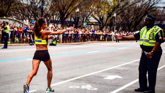 Danna Herrick acknowledges a police officer during the Boston Marathon on April 17.