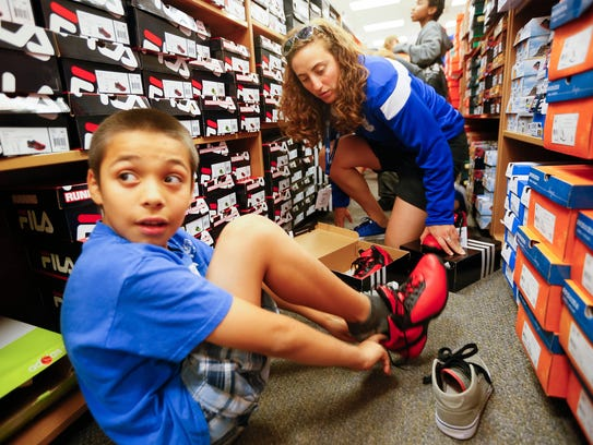 Javier Morales, 9, tries on a pair of shoes with help from Jacqui Kalin, a member of the Drake women's basketball team at Kohl's in 2015.