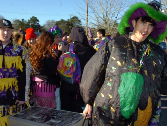 Revelers prepare to board colorfully decorated floats