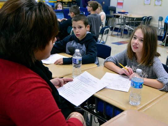 Teacher Crystina Warner, left, works with students