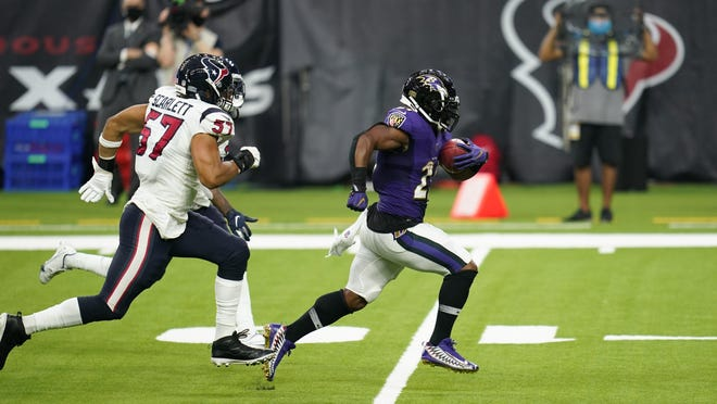 Baltimore Ravens running back Mark Ingram breaks free from Houston Texans defenders during Baltimore's 33-16 win Sunday. The Ravens gashed Houston for 230 rushing yards in the victory.