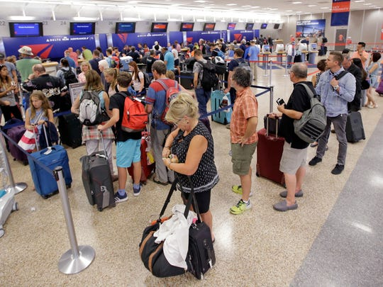 Delta Air Lines passengers stand in line after flights resumed Monday, Aug. 8, 2016, in Salt Lake City, following a computer outage.