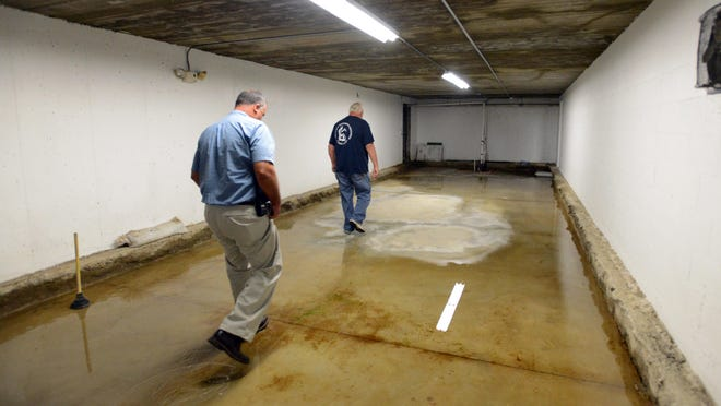 Ed Wolfe, left, and Tim Dufner walk through a water-filled tunnel underneath General Sherman Junior High School in Lancaster. Dufner said the tunnels, originally used for storage for the building and the district maintenance department, have been flooding for six to eight years despite the installation of four sump pumps.