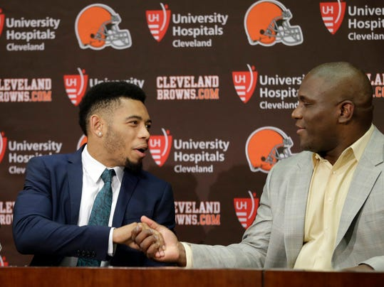 Cleveland Browns cornerback Joe Haden, left, shakes hands with general manager Ray Farmer at the start of a news conference at the NFL football team's facility in Berea, Ohio Wednesday, May 14, 2014. Haden signed a five-year contract extension with the Browns Tuesday. (AP Photo)
