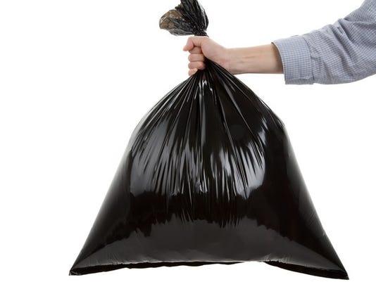getty-hand-holding-black-trash-bag_large.jpg