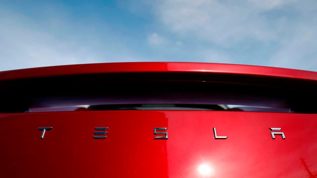 In this April 15, 2018 file photo, the sun shines off the rear deck of a roadster on a Tesla dealer's lot in the south Denver suburb of Littleton, Colo. Tesla has picked Austin, Texas, and Tulsa, Oklahoma, as finalists for its new U.S. assembly plant, a person briefed on the matter said Friday.