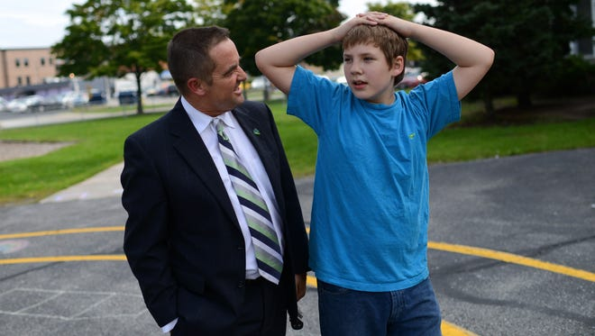 Green Bay Mayor Jim Schmitt meets Aiden Gervais, 11 behind Aiden's school on Wednesday. The two were matched up through the Big Brothers/Big Sisters program and meet for about an hour every week.