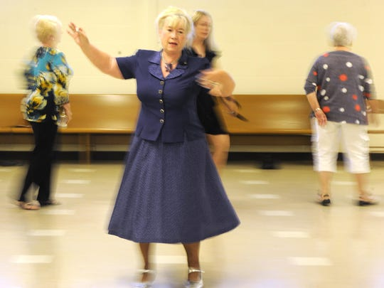 Carolyn England, 65, teaches her ballroom dancing class new steps Thursday evening at Holy Trinity Lutheran Church. England took up ballroom dancing after raising her sons and retiring from 22 years of working at the post office.