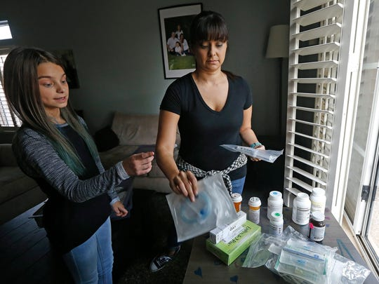 Nicole Robinson, right, with daughter Riley, 11, go over the variety of medications Riley is required to take on a daily basis Thursday, Oct. 27, 2016, in Cave Creek, Ariz. Americans in the health insurance markets created by President Barack Obama's law will have less choice next year than any time since the program started, with the Phoenix market being hardest hit by insurer exits, shrinking from nine carriers to one, with many other communities affected, with families like the Robinsons who will have even higher rising premiums announced earlier this week.