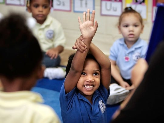 A student tries to catch the attention of her pre-K teacher to answer a question in this file photo.