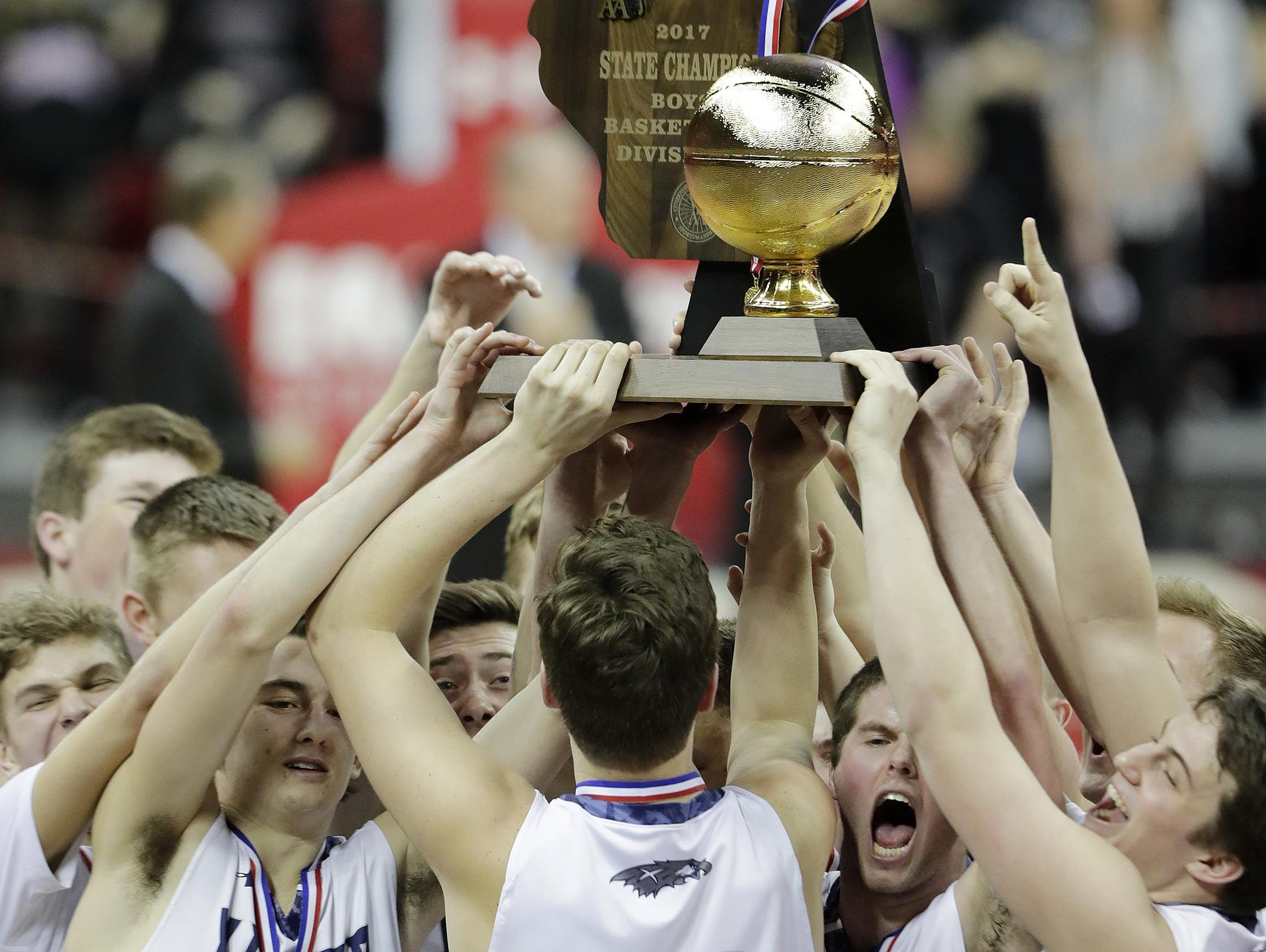 Xavier players celebrate with the trophy after the Division 3 championship game against Prescott on Saturday at the Kohl Center in Madison. See more photos at postcrescent.com.