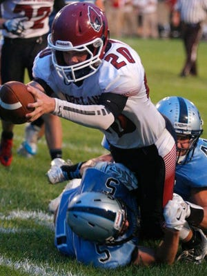 Portland's Gabe Schrauben, top, dives over the goal line for a touchdown against Lansing Catholic's Nic Baker (5), and Ben Rashid Friday, Sept. 18, 2015, in Holt, Mich.
