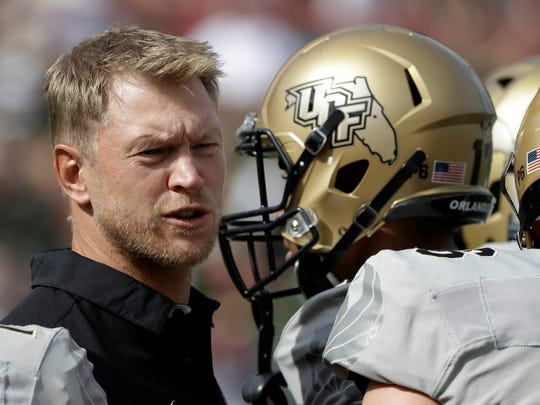 FILE - In this Nov. 26, 2016, file photo, Central Florida head coach Scott Frost, left, talks to his team during the first quarter of an NCAA college football game against South Florida, in Tampa, Fla.  American Athletic Conference Commissioner Mike Aresco's dream of a true P6 seems unlikely to ever come to fruition, but if coaches like Morris, Montgomery, Norvell, Frost, Collins and Applewhite can be as successful as Herman, Rhule, Taggart and Fuente the future of the American has a chance to be more lucrative.   (AP Photo/Chris O'Meara, File)