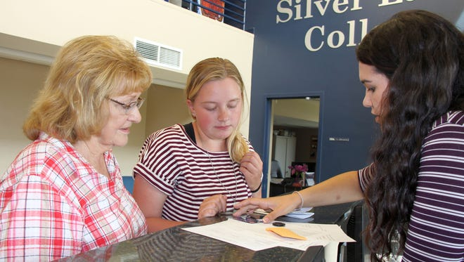 Silver Lake College student Carla Martinez Morant, right, welcomes freshman Tekla Kilpatrick of Little Chute as she checks into the dorm, while her grandmother, Clarice Van Kleeck, looks on. Silver Lake College welcomes 95 freshmen this fall, the largest incoming freshman class in its 82-year history.