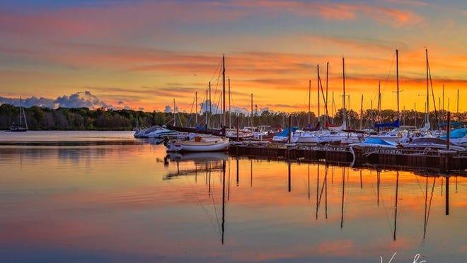 Sunrise over the Presque Isle Marina .