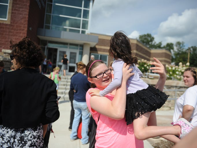 Fifth-grader Gwyn Kreider lifts family friend Mikayla Girard after the end of classes for Kreider at Coshocton Elementary School. Girard will start kindergarten later this week.