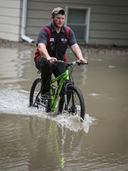 Teran Cozad rescued a bicycle out a garage for a friend who lives in a a flooded apartment building along 75th Street in Clive Thursday, June 25, 2015.