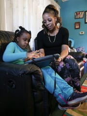 Clara Washington asks her daughter, Jayla Morrison, 7, to point to the symbol for Cheerios on the tablet. Jayla has autism and is considered nonverbal.