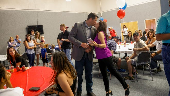 GOP sheriff candidate Shane Ferrari kisses his wife Brandie Ferrari as early results show him taking a big lead over Tommy Bolack Tuesday during Ferrari's primary election party at the Fraternal Order of Police building in Farmington.