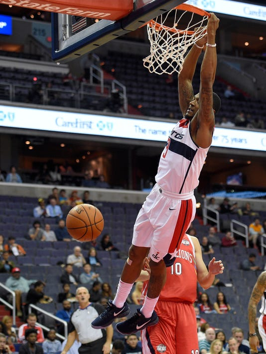 Washington Wizards guard Bradley Beal (3) hangs from the rim after a dunk in front of Guangzhou Long-Lions' Zhu Xuhang (10) during the first half of an NBA basketball exhibition game, Monday, Oct. 2, 2017, in Washington. (AP Photo/Nick Wass)