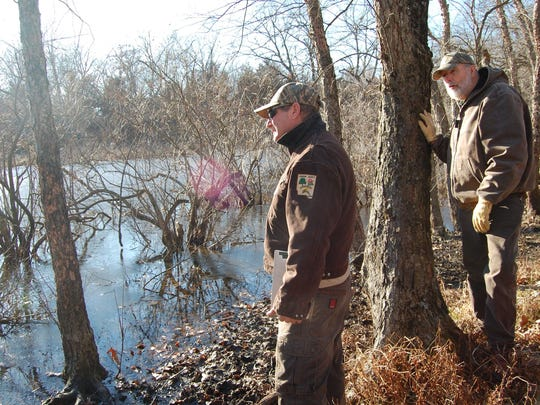 Former Johnson County Conservation Board vegetation specialist Dave Wehde, left, and former director Harry Graves inspect a pond on Jan. 9, 2012, at the county's Ciha Fen Preserve near Sutliff.