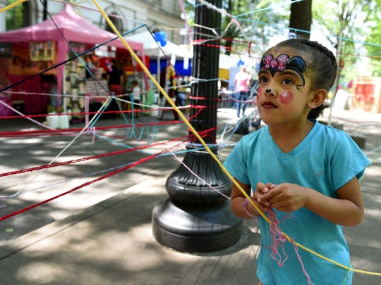 "Bella Bradley, 4, looks at her grandmother while playing in the ""yarn tangle"" at the 2016 Dogwood Arts Festival in Downtown Knoxville Friday, April 29, 2016."