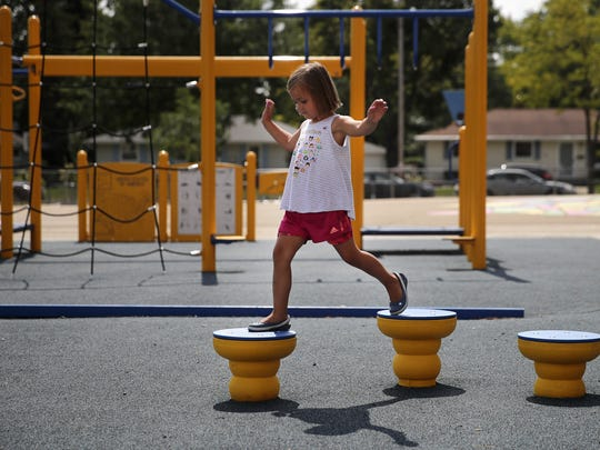 Caitlin Locy, 4, steps from one platform to another at the Huntley Elementary School playground. The playground was funded by community development block grants through the federal budget.