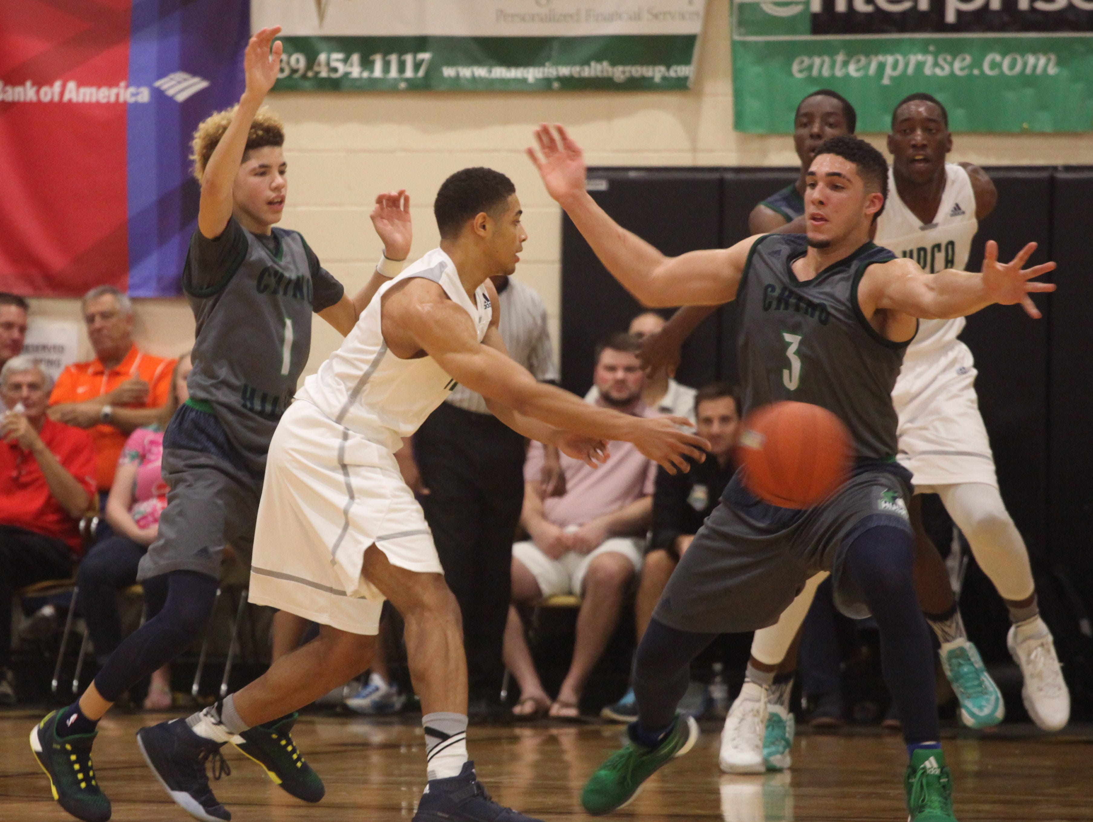 Chino Hills' LaMelo Ball, left, and LiAngelo Ball put up some heavy defense against High Point Christian Academy's Ty Graves during the City of Palms Semifinal on Tuesday night.