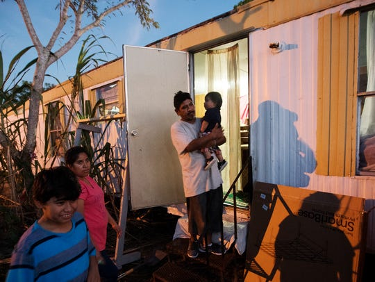 From left, Jody Paz-Cruz,11, Maria Paz, Antonio Hernandez-Cruz, and Jay Paz Cruz,13, mos, are seen outside of their trailer at the Saldivar Mobile Home Park in Bonita Springs on Wednesday evening. The family was rendered homeless due to flooding from an August storm and Hurricane Irma. The spent nearly two months in area shelters.