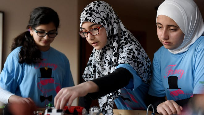 Tuba Ali, 12, (left to right), Halima Niazi, 12, and Nura Salen, 11, with the 'Fancy Flamingos'  First Lego League team demonstrate how their programmed robots score points.