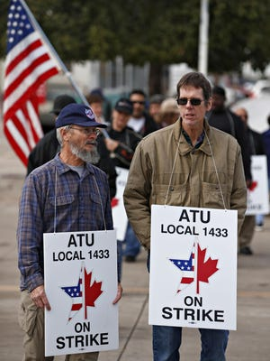 Bus drivers represented by Amalgamated Transit Union Local 1433 walk a picket line on Friday, Jan. 8, 2015, outside the Valley Metro holding yard on Lower Buckeye Road in Phoenix.