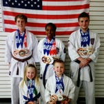 Camryn Bullock on podium at national karate championships after earning a first place victory in fighting.